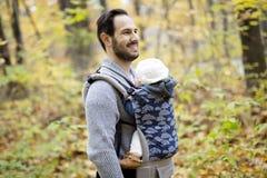 有女儿婴孩的父亲在秋天森林里 库存照片