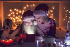 有女儿开放圣诞节礼物的妈妈 免版税图库摄影