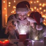 有女儿开放圣诞节礼物的妈妈 库存照片