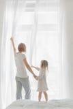 有女儿开窗口帷幕的年轻母亲 库存照片