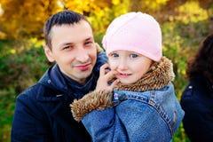 有女儿的一个父亲在秋天森林里 图库摄影