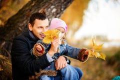 有女儿的一个父亲在秋天森林里 免版税库存图片