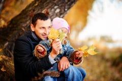有女儿的一个父亲在秋天森林里 库存照片