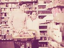 有女儿的妇女在超级市场 库存照片