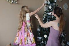 有女儿的妈咪装饰圣诞树,为圣诞节做准备,装饰,装饰,生活方式,家庭,家庭价值观 免版税库存照片