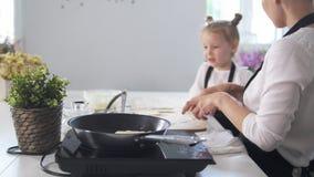 有女儿的妈妈在早晨厨房-妇女做酸奶干酪薄煎饼解释烹调技术 股票视频