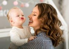 有女儿的妈妈她的胳膊的在家情感地拥抱她 免版税库存图片