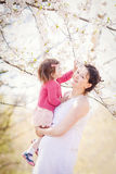 有女儿的孕妇在公园 库存图片