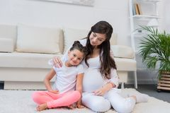 有女儿的孕妇坐地毯 免版税库存照片