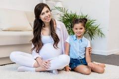 有女儿的孕妇坐地毯 图库摄影