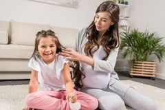 有女儿的孕妇坐地毯 免版税库存图片