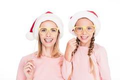 有女儿的愉快的母亲圣诞老人帽子的和纸板集会在圣诞节的玻璃, 图库摄影