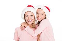 有女儿的愉快的母亲拥抱在圣诞节的圣诞老人帽子的, 免版税库存照片