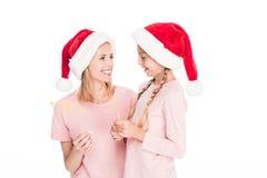 有女儿的愉快的母亲拿着纸板的圣诞老人帽子的集会在圣诞节的玻璃, 图库摄影