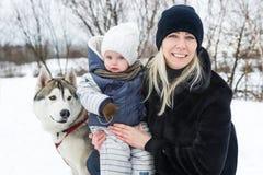 有女儿的愉快的年轻母亲在有爱斯基摩狗的冬天公园 库存照片