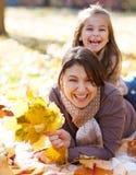 有女儿的愉快的年轻母亲在秋天公园 免版税库存照片