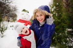 有女儿的母亲修造了雪人并且高兴 免版税库存照片