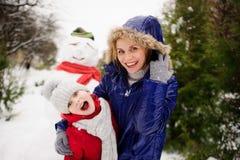 有女儿的母亲修造了雪人并且高兴 库存照片