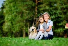 有女儿的母亲和拉布拉多是在草 免版税库存图片