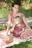 有女儿的母亲坐一棵草在公园 免版税图库摄影
