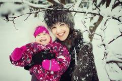 有女儿的母亲获得乐趣在冬天公园 图库摄影