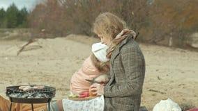 有女儿的母亲,外套的一年轻女人坐海滩由河,海洋,做了野餐,厨师菜和 股票录像