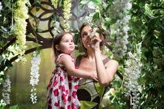 有女儿的母亲 绿色花卉庭院 免版税库存图片