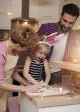 有女儿的父母在厨房里 库存图片