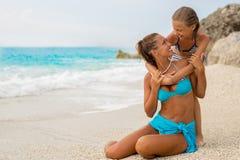 有女儿的美丽的年轻母亲海滩拥抱的 库存图片