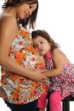 有女儿的讲西班牙语的美国人怀孕的母亲 库存照片