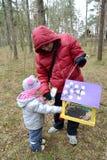 有女儿的年轻人在鸟饲养者投入了五谷 图库摄影