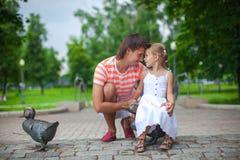 有女儿的年轻愉快的父亲在公园有 图库摄影
