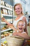 有女儿购买的母亲在超级市场使食物变冷 免版税图库摄影