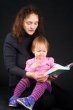 有女儿阅读书的母亲 库存照片