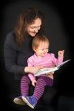 有女儿阅读书的俏丽的母亲与 库存照片