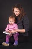 有女儿阅读书的俏丽的母亲 免版税库存图片