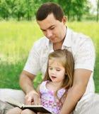 有女儿读书的父亲在公园 免版税图库摄影