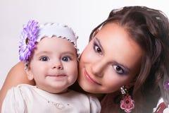 有女儿滑稽微笑的美丽的母亲。婴孩6个月 免版税库存照片