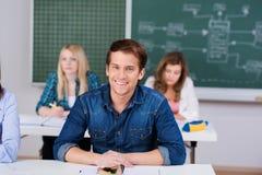 有女同学和老师的男学生在背景中 免版税库存照片