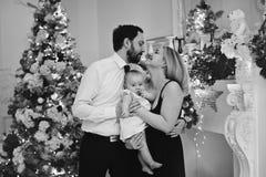 有女婴的愉快的父母在圣诞节的装饰的屋子里 图库摄影