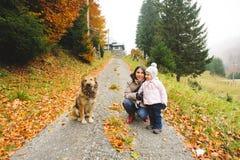 有女孩和狗的母亲 库存图片