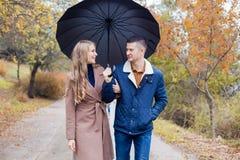 有女孩的一个人去在伞雨下 免版税库存图片