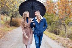 有女孩的一个人去在伞雨下 库存图片