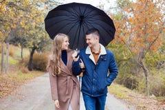有女孩的一个人去在伞雨下 免版税库存照片