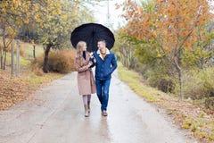 有女孩的一个人去在伞雨下 免版税图库摄影