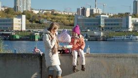 有女孩的一名妇女,有一个女儿的一个母亲,内河港的,吃午餐,有气球的一个孩子 影视素材
