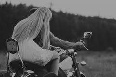 有女孩的人在摩托车的一个领域的 库存照片