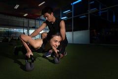有女孩的健身辅导员训练的在健身中心,做俯卧撑的少妇射击在健身房 肌肉女性做的p 免版税库存图片
