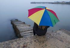 有女孩的明亮的伞在海滩的有薄雾的天 图库摄影
