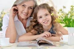 有女孩读书杂志的祖母 库存照片